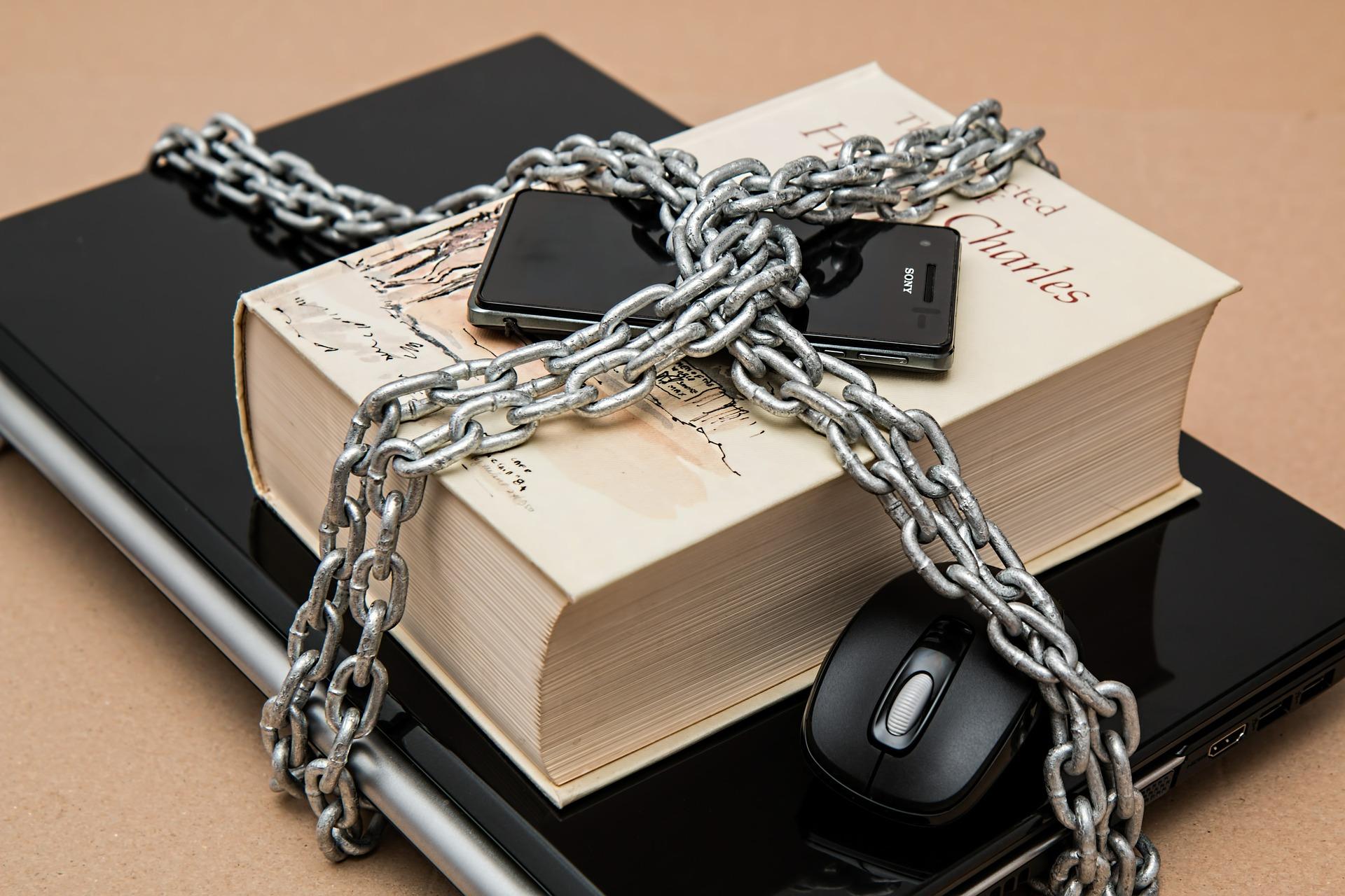 Ordenador, libro y móvil encadenado